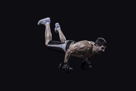 muscular build: Athlete performing no legs push ups on dumbbells isolated on black background