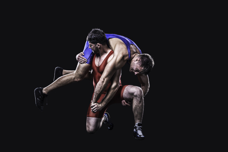 Two freestyle wrestlers in red and blue wrestling uniform isolated on black background