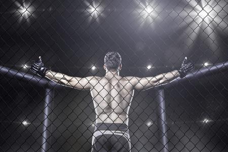 luchador de MMA en la jaula de la victoria celebrando, vista desde atrás