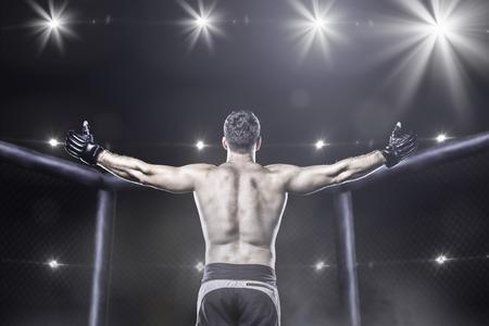 Luchador de MMA en la jaula después de la victoria, detrás de vista Foto de archivo