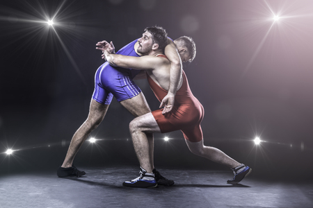 Two freestyle wrestlers in red and blue uniform wrestling against the lights on background