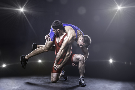 wrestlers: Two freestyle wrestlers in red and blue uniform wrestling against the lights on background