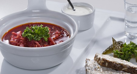 salo: Ukrainian national red borscht soup served with a sour cream, salo sandwich and salty cucumbers decorated with parsley on white plate Stock Photo