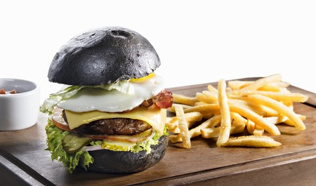 high calorie: Black burger with fried egg and french fries on wooden board isolated on white background