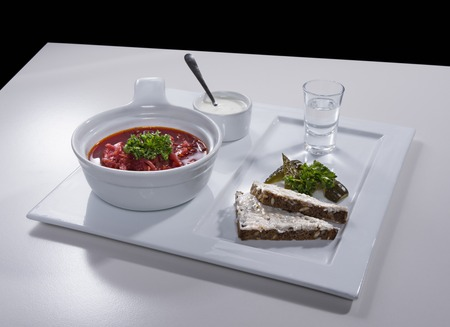 salo: Ukrainian national red borscht soup served with a sour cream, black bread sandwich with salo and salty cucumbers decorated with parsley on white square plate