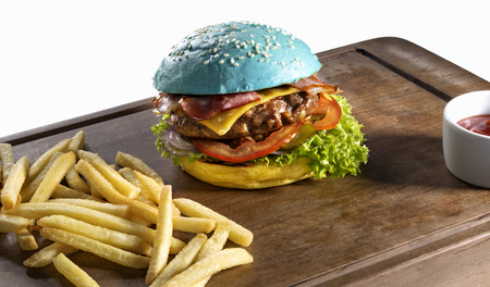 high calorie: Yellow blue color burger with french fries on wooden board on white background