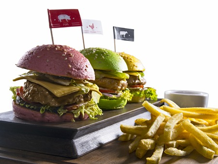 high calorie foods: Different color burgers with beef, pork and chicken with french fries on wooden board isolated on white backgound Stock Photo