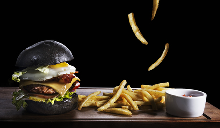 high calorie: hamburger with fried egg and french fries on wooden board isolated on black background Stock Photo