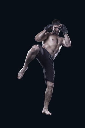 mixed martial arts: mma fighter hitting with knee isolated on black background