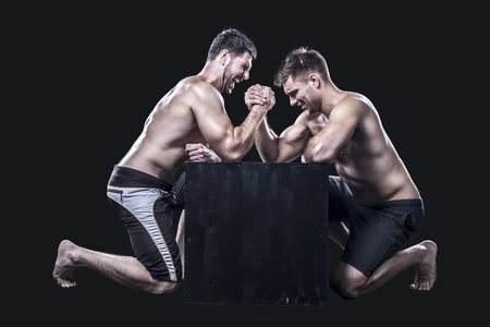 dois: Dois armwrestlers, têm um fósforo wrestling de braço em uma caixa preta sem camisa Imagens