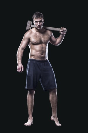 Athlete with a sledgehammer isolated on black background