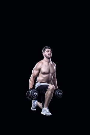 knee bend: Shirtless sportsman doing knee-bends with dumbbells isolated on black background