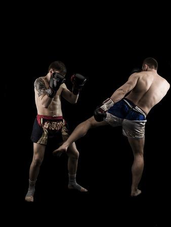 men exercising: Dos hombres caucásicos que ejercen fondo negro tradicional de artes marciales