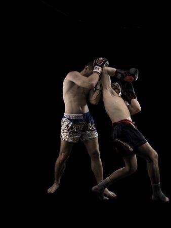 men exercising: Two caucasian men exercising muay thai isolated on black background