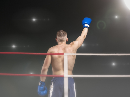 Young boxer in blue boxing gloves celebrating victory