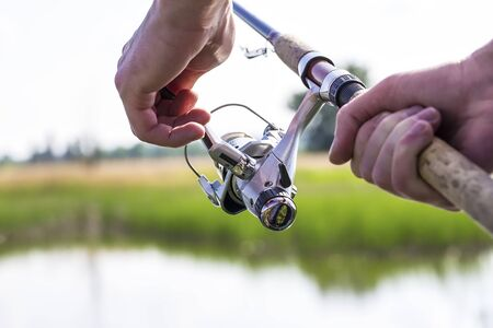 Fisherman start to fishing by spinning on river in sunny weather Stock Photo