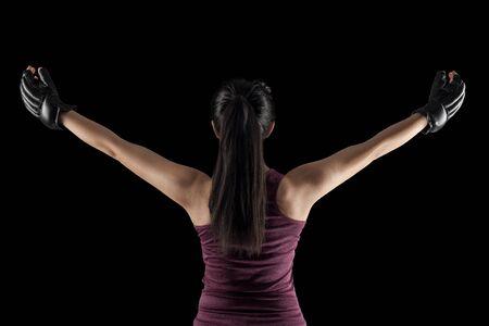 combatiente femenina mma con las manos levantadas, vista desde la parte posterior, aislado en fondo negro Foto de archivo
