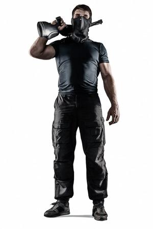infantryman: Man in headgear wearing black military uniform holding rifle isolated on white background Stock Photo