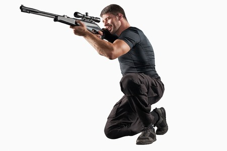 aiming: man in black military uniform aiming with rifle isolated on white background Stock Photo
