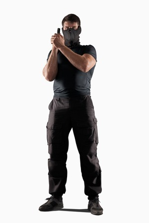 man in black uniform and headgear with gun in prepared position isolated on white background Stock Photo