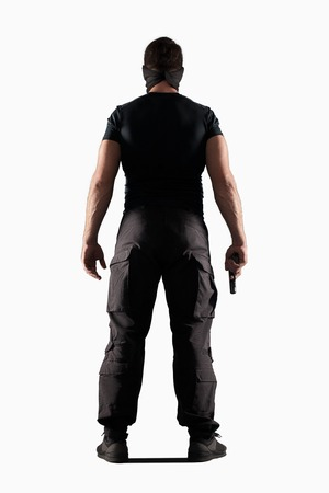 黒の制服と白い背景、リアビューに分離された銃を持つ帽子の男
