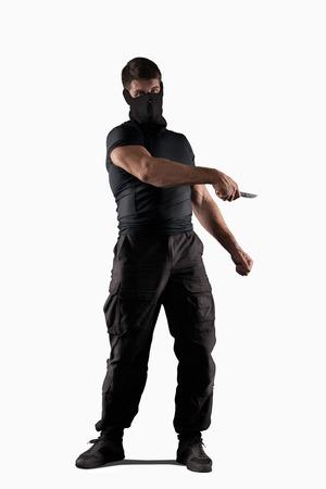 Mann in der schwarzen Uniform mit Messer angreift isoliert auf weiß