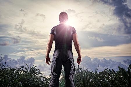 Man in headgear and black military uniform standing with gun on sunny sky background 版權商用圖片