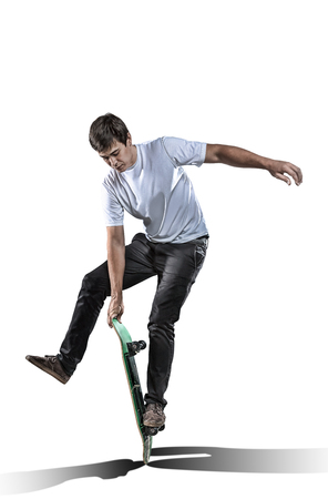 Skateboarder is performing freestyle trick isolated on white background