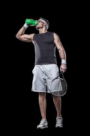 actividades recreativas: agua potable del jugador de tenis deportivo después de un partido de tenis aislado en negro