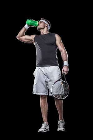 athletic tennis player drinking water after tennis match isolated on black