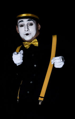 Male mime in black shirt and hat isolated on black background