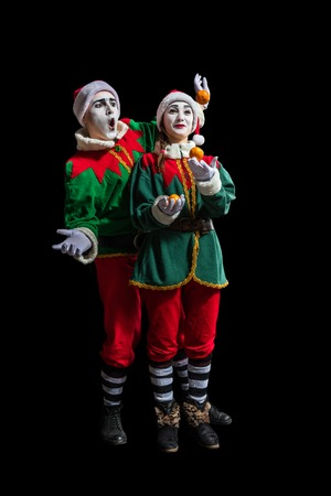 Couple of mimes in New Year costumes posing isolated on black background Stock Photo