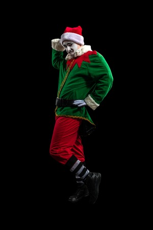 Male mime in New Year costume posing isolated on black background