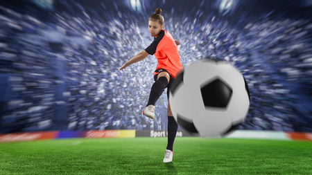 female football player in orange uniform kicking the ball