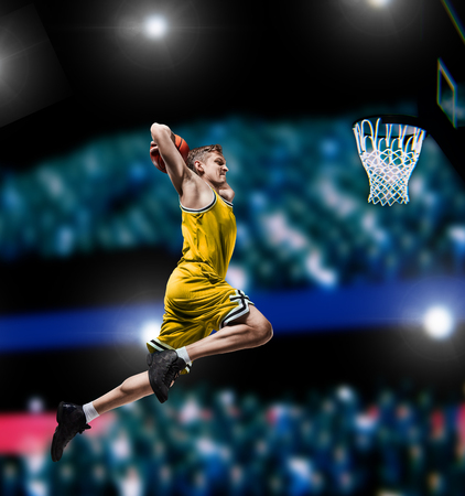 basketball player making slam dunk on basketball arena Stock Photo