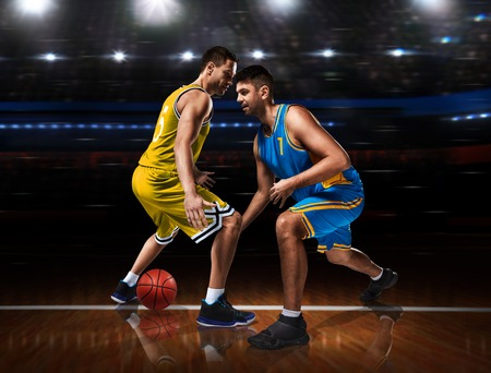 two basketball players in scrimmage on basketball court