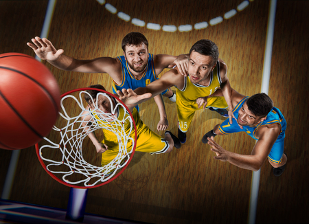 four basketball players during scrimmage on nasketball arena Imagens