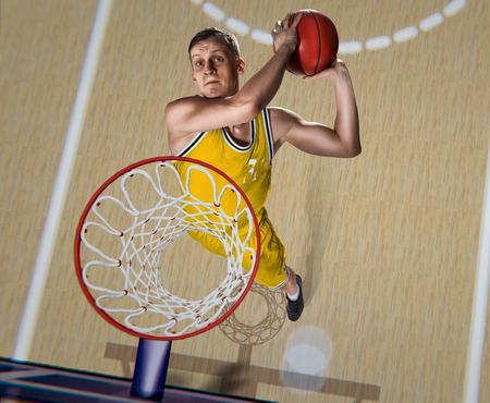 basketball player making slam dunk on basketball arena Imagens