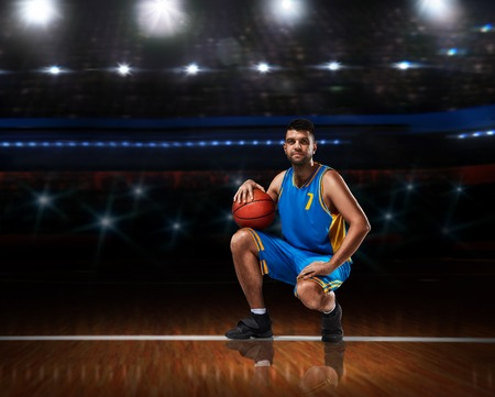 basketball player in blue uniform sitting on basketball court 스톡 콘텐츠