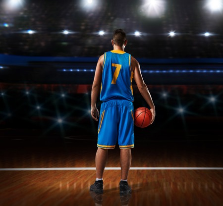 basketball player in blue uniform standing on basketball court
