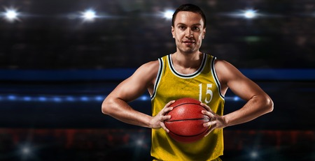 basketball player in yellow uniform standing on basketball court