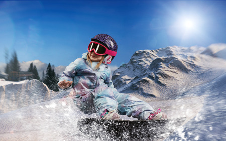 little snowboarder girl riding snowboard in the mountains