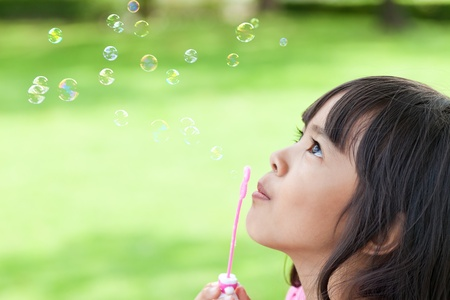 blowing bubbles: Little Girl Blowing Soap Bubbles Stock Photo