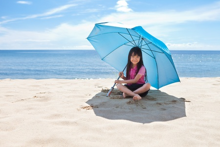 beach umbrella: Little girl at beach with blue umbrella  Stock Photo