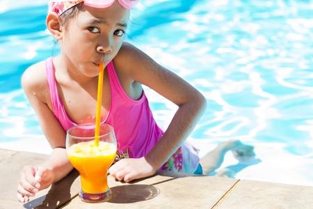 Little girl at swimming pool drinking orange juice photo