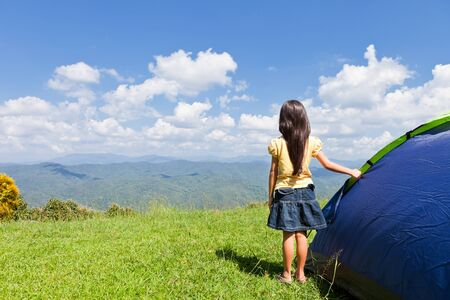 little girl barefoot: Little girl with tent on mountain