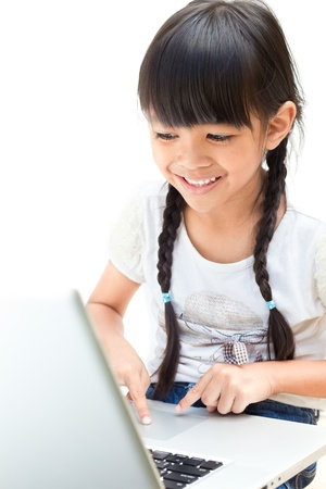 Cute little asian girl using laptop isolated on white photo