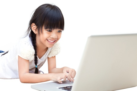 Happy and smiling little girl with laptop isolated on white photo