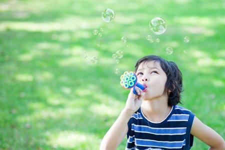 burbujas de jabon: Ni�o soplando burbujas de jab�n Foto de archivo