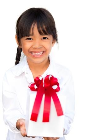 generoso: Sonriente niña sosteniendo y que ofrece un regalo, aisladas sobre fondo blanco